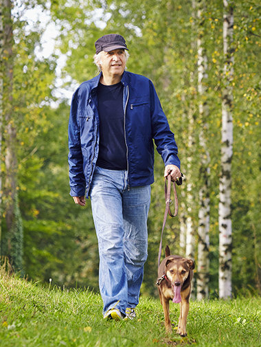 Dog walking on a lead in grass with owner
